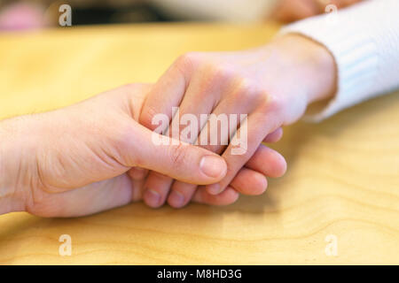 A man's hand holds a woman's hand. Manifestation of love, care and friendship. - Stock Photo