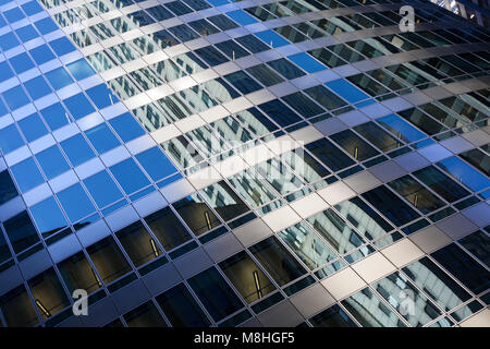 Closeup of modern building with refection of nearby skyscrapers - Stock Photo
