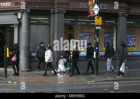 Manchester, UK, 17 Mar 2018. A homeless man wrapped in foils sits on the pavement as people wearing St Patricks - Stock Photo