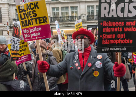 London, UK. 17th March 2018. A man in a red hat, gloves and shirt holds two holds two placards on the march through - Stock Photo