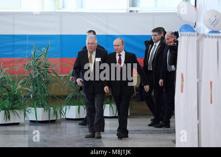 Moscow. 18th Mar, 2018. Russian President Vladimir Putin (R F) arrives at a polling station for voting in Moscow - Stock Photo