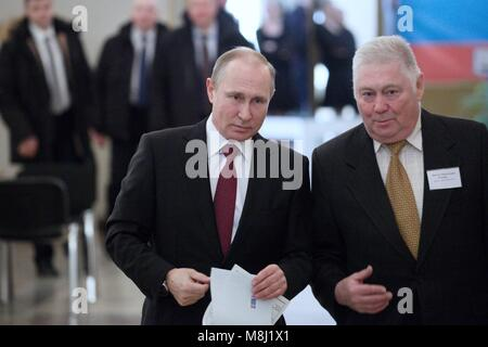 Moscow. 18th Mar, 2018. Russian President Vladimir Putin (L) prepares to vote at a polling station in Moscow March - Stock Photo