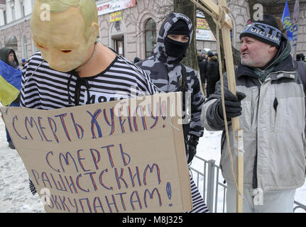 Kyiv, Ukraine. 18th Mar, 2018. A participant of embassy blocking holds a hanged effigy, depicting Russian President - Stock Photo