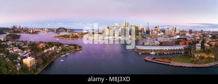 Colourful sunset over Sydney city CBD landmarks from North Sydney through Barangaroo to Darling harbour in aerial - Stock Photo