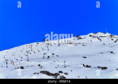 Back Perither mountain peak and infrastructure of chair lifts bringing skiers and snowboarders up to the top during - Stock Photo