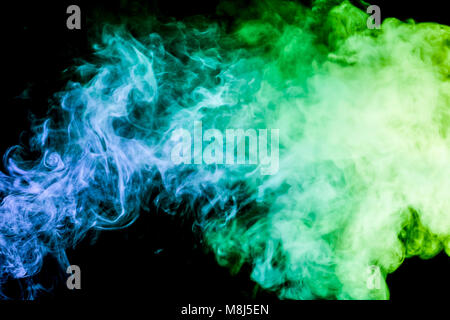 Colorful smoke of  green and blue on a black isolated background. Background from the smoke of vape - Stock Photo