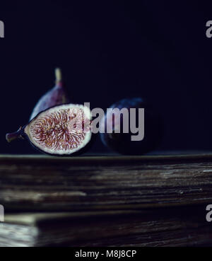 Ripe Figs Positioned on Top of Antique Books - Stock Photo
