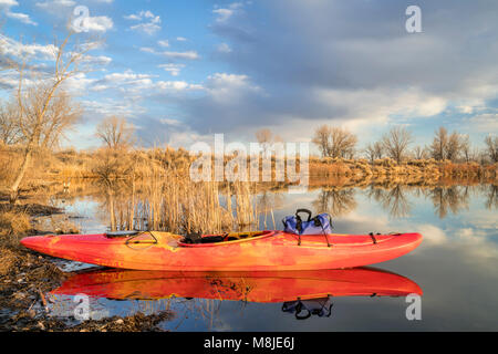 whitewater kayak on a calm lake in Colorado, early spring scenery - Stock Photo