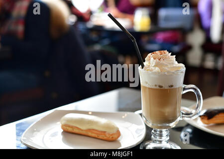 coffee with whipped cream and eclair on the table in a cafe - Stock Photo