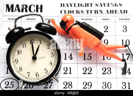 Daylight Savings Spring Forward sunday at 1:00 a.m. March 25 date indicated in the calendar. Clock next to a toy - Stock Photo
