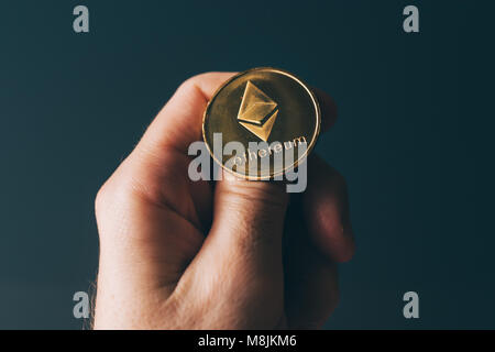 Ethereum cryptocurrency in hand, blockchain technology decentralized currency coin - Stock Photo