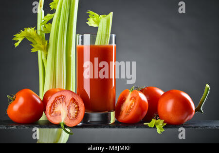 Tomato juice or cocktail bloody Mary with tomatoes and celery sticks on a dark background. Copy space. - Stock Photo