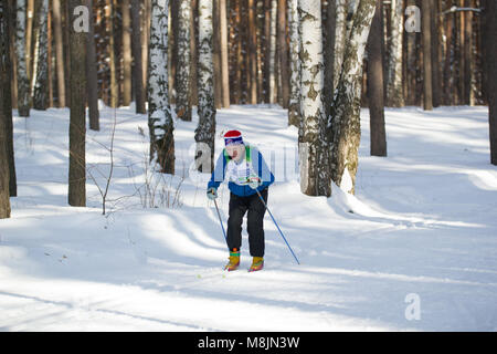 KAZAN, RUSSIA - March, 2018: old man running ski marathon in sunny frozen forest - Stock Photo