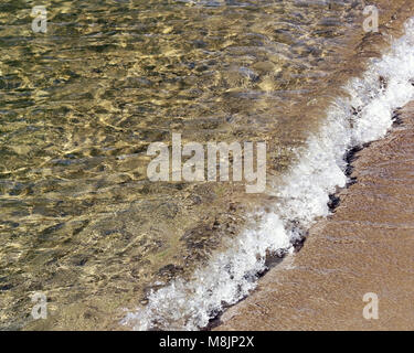 Soft wave rolling onto sandy shore - Stock Photo