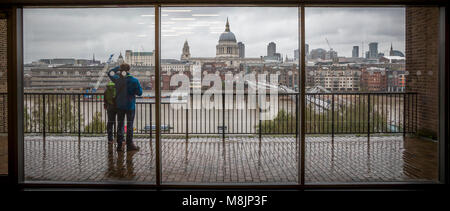 A couple study a schematic and take in the view from Tate Modern across the Thames showing Foster's Millennium Bridge - Stock Photo