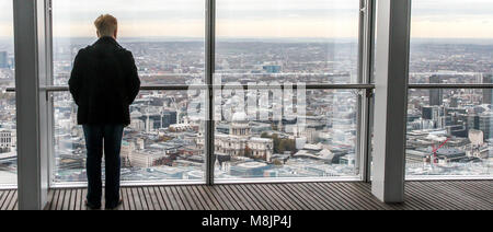 A solitary figure surveys the vertiginous view across London from the top of The Shard's viewing platform - Stock Photo