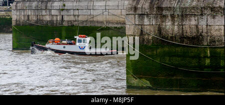 Tower Bridge's massive chained cutwaters with working tug boat Devoted passing between them in choppy Thames water - Stock Photo