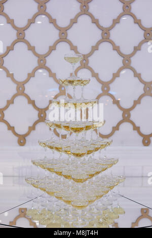 Pyramid of wine glasses with champagne on a buffet table - Stock Photo