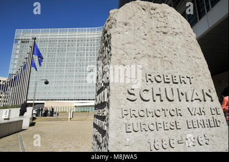 Robert Schuman monument and EU flags in front of Berlaymont building, headquarters of the European Commission, on - Stock Photo
