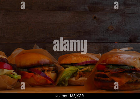 Many big fresh tasty burgers on dark wooden background with copy space for text - Stock Photo