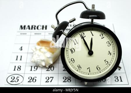 Daylight Savings Spring Forward sunday at 1:00 a.m. March 25 date indicated in the calendar. Clock next to a conch. - Stock Photo