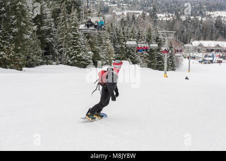Snowboarder heading down the run at  Whistler Blackcomb ski resort, British Columbia. - Stock Photo