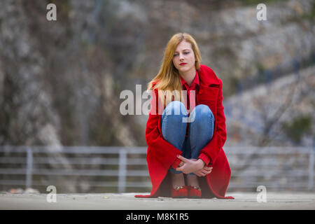 Beautiful teenager girl denim pants legs Red high heels shoes - Stock Photo
