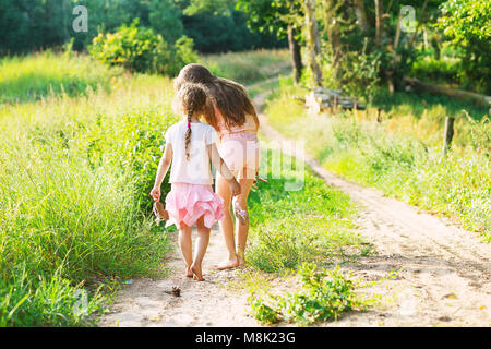 Two little sisters walking and playing on the road in countryside on a warm summer sunset. Cute little girls. Back - Stock Photo