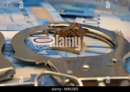 white small paper house tied with chain to the money golden coins, loan money secured by immovable property concept, - Stock Photo