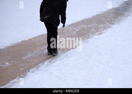 A boy in a green jacket and striped cap slides on an ice slide - Stock Photo