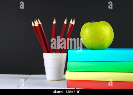 A Pile Of Books And Stationery On Chalkboard Background Work Desk Education