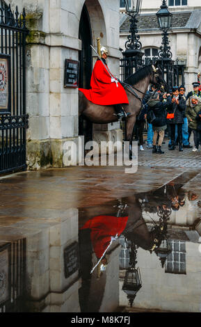 Horse Guard outside the Household Cavalry Division in Whitehall surrounded by tourists on a cold day - Stock Photo