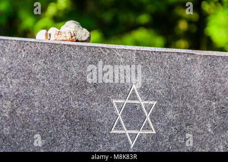Stones on Jewish Memorial granite plate with Star of David. It is a Jewish tradition to take small stones and leave - Stock Photo
