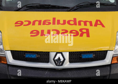 The word Ambulance Rescue written frontbackwards on the front of ambulance car - Stock Photo