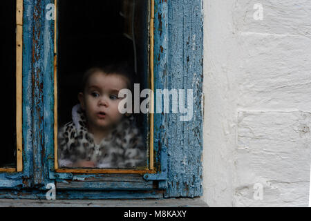A little girl sits in an old hut on a window on which the paint faded - Stock Photo