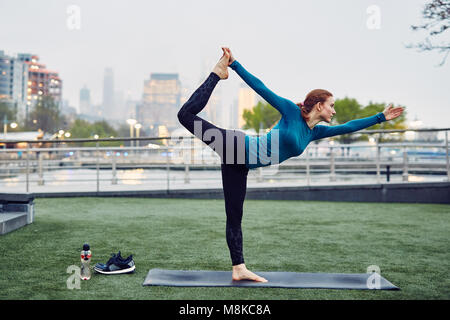 Caucasian Woman Performs Yoga in a Public New York City Park - Stock Photo