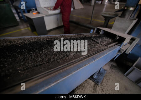 Rubber pellets on a conveyor belt on a schredder that recycles used car tires at a scrapheap junkyard - Stock Photo