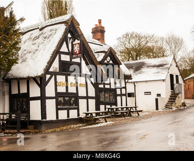 Snow covered black and white half timbered houses and the White Lion  inn in the picturesque  Cheshire village of - Stock Photo