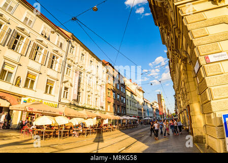Graz, Styria / Austria - 07 09 2016 : View on Herrengasse main street in the city center, tourists walk in sunset. - Stock Photo