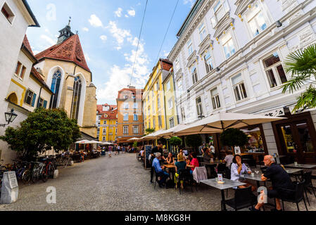 Graz, Styria / Austria - 07 09 2016 : One of colorful alleys in Graz city with historical buildings church and restaurants - Stock Photo