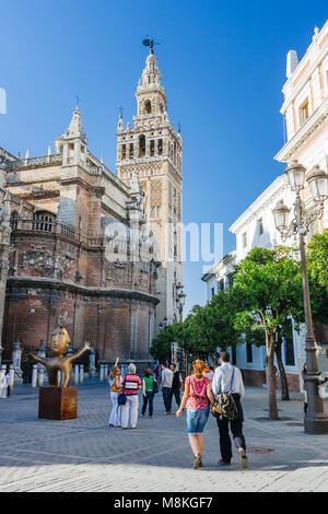 Seville, Andalusia, Spain : Tourists walk towards the Gothic Cathedral and Giralda bell tower in Plaza del Triunfo - Stock Photo