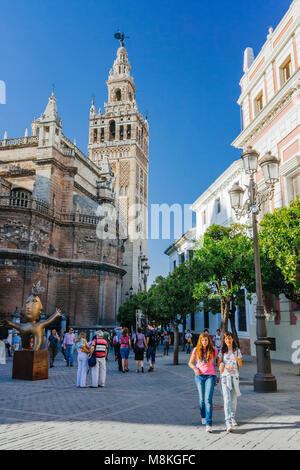 Seville, Andalusia, Spain : People walk past the Gothic Cathedral and Giralda bell tower in Plaza del Triunfo square. - Stock Photo