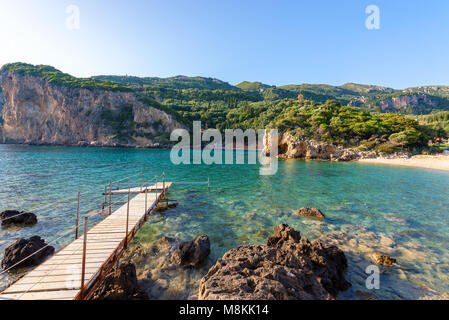 Wooden pier in Paleokastritsa bay with sand and crystal sea water. Corfu island, Greece. - Stock Photo