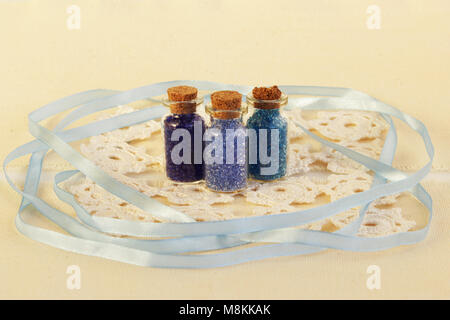 Three tiny glass bottles with a cork stopper, filled with a blue colours of beads, white knitted napkin and blue - Stock Photo