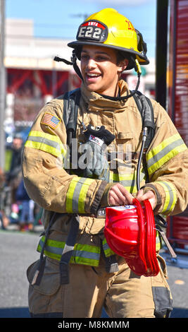 A fireman in the St. Patrick's Day Parade in Bellingham, Washington on March 17, 2018.  The fireman is giving out - Stock Photo