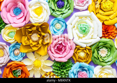 Colorful paper flowers on wall. Handmade artificial floral decoration.  Spring abstract beautiful background and - Stock Photo