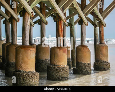 DAYTONA BEACH, FLORIDA - APRIL 15, 2017: A large accumulation of barnacles can be seen on the concrete pillars of - Stock Photo