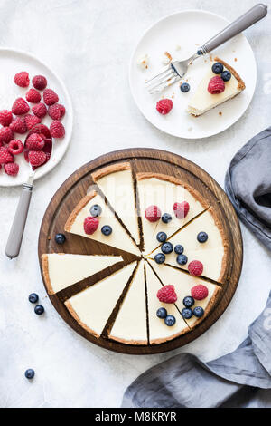 Classic New York cheesecake with fresh raspberries and blueberries on white concrete background, top view - Stock Photo