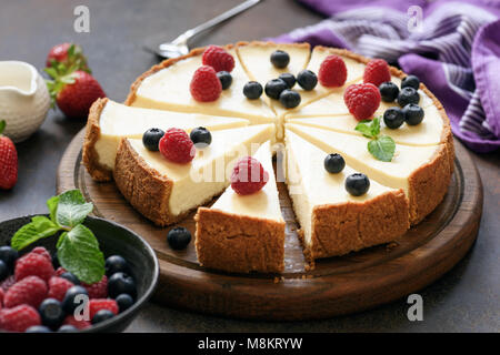 Classic plain New York Cheesecake sliced on wooden board, closeup view, selective focus - Stock Photo