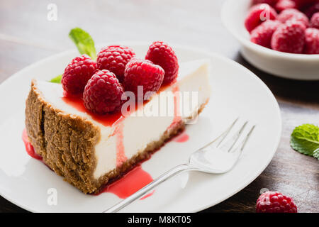 Cheesecake with raspberries and berry sauce on white plate, closeup view, selective focus. Slice of cheesecake - Stock Photo